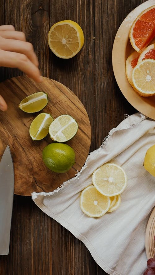 A Person Cutting a Lime into Slices by Using a Knife