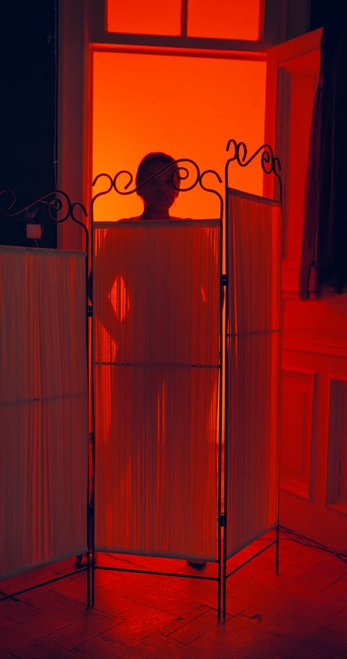 Silhouette of a Woman Against Red Light Background