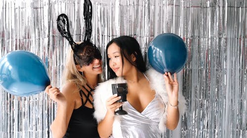 Two Women Happily Looking at Each Other While Holding Blue Balloons