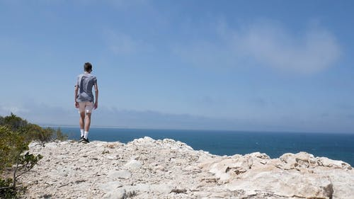 A Man Standing on a Cliff Edge
