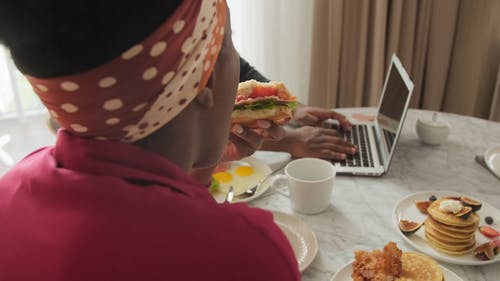 A Woman Eating Her Sandwich While a Man Using His Laptop