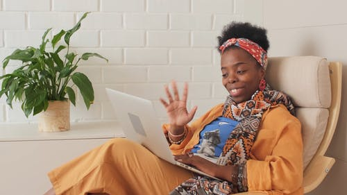 A Woman Sitting on an Armchair While Having a Video Conference through Her Laptop
