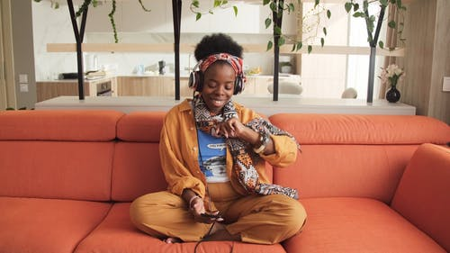 A Woman Sitting on Orange Couch While Dancing and Having Fun