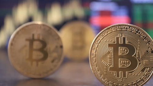 Bitcoin Gold Coins with Financial Chart Background