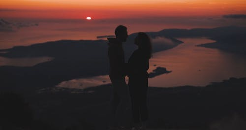 A Couple Kissing On The Mountain Top