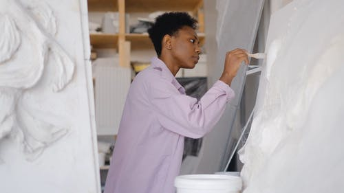 A Woman Painting Using a Paintbrush