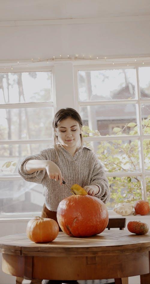 A Woman Carving A Pumpkin For Halloween