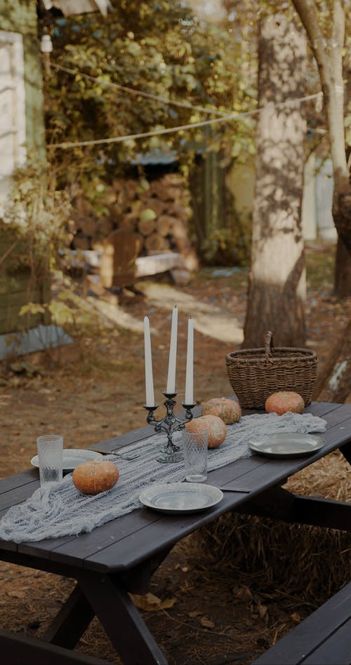 A Woman Setting A Halloween Theme Table Outdoors