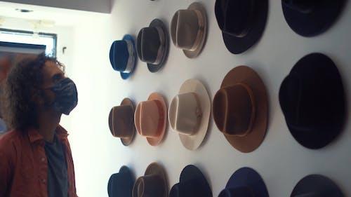 Man Looking at Hats