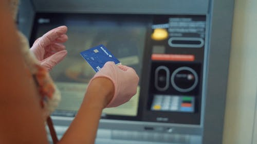 Woman Inserting Card on a Machine