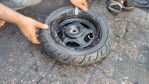 Faceless Man Repairing a Tire