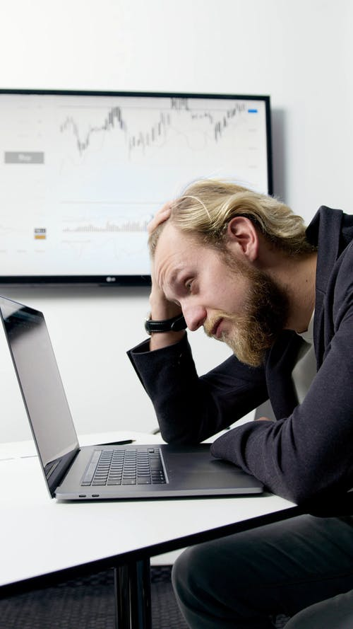A Man Looking Problematic while Looking at His Laptop