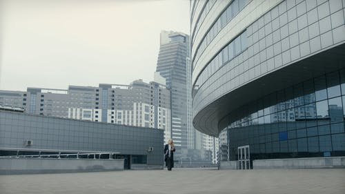 A Woman Walking Outside Of A Building