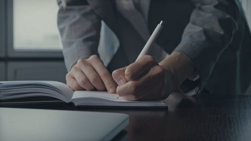 A Woman Writing On Her Planner