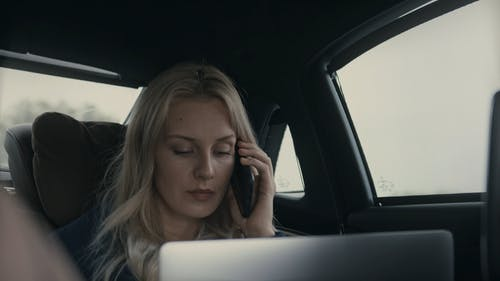 A Woman Talking On Her Cellphone Inside A Moving Car