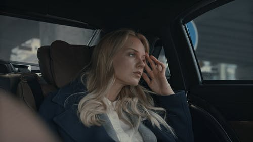 A Woman Feeling Fatigue At The Back Of A Car