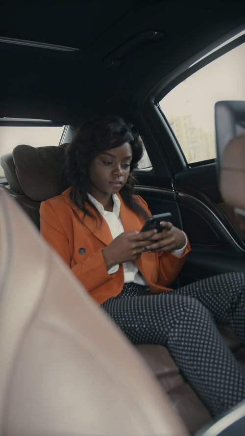 A Woman Using Her Phone Inside A Moving Car