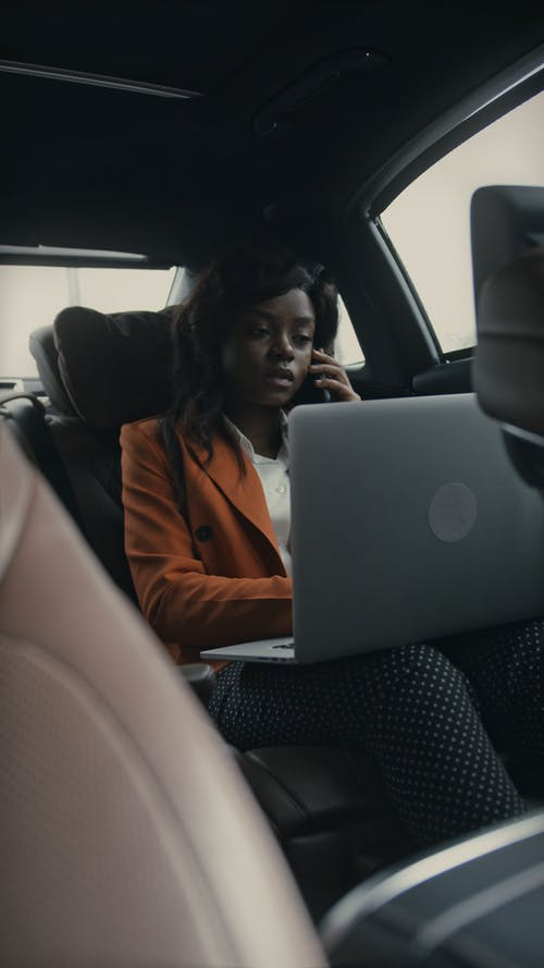 A Woman Working While Inside A Moving Car