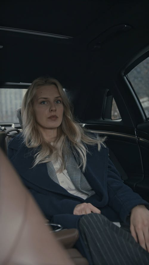 A Woman Sitting At The Backseat Of A Car