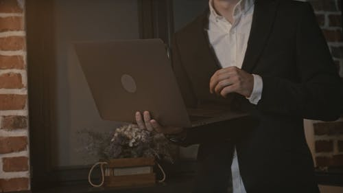 Young Man Standing and Using Laptop