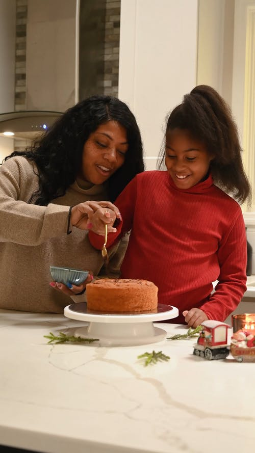 Mom and Daughter Decorating a Cake with Chocolate