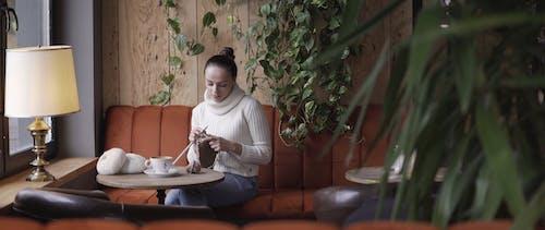 A Woman Knitting Inside a Coffee Shop