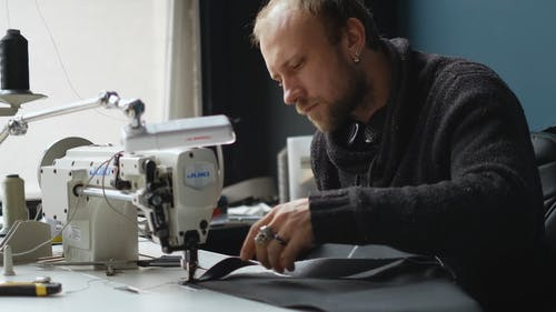 A Tailor Sewing a Garment