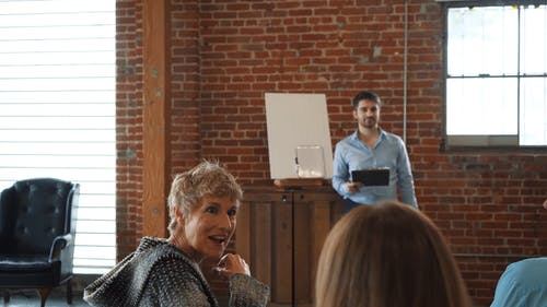 Woman in Knitted Long sleeves Having a Conversation to the Blond Woman While Men are Listening