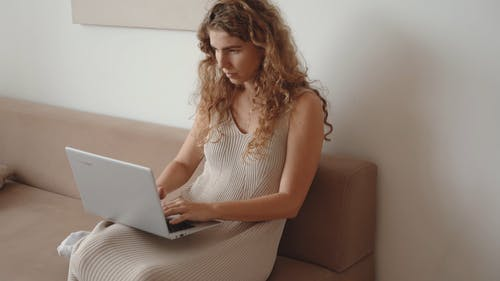 Woman on the Couch Typing in a Laptop