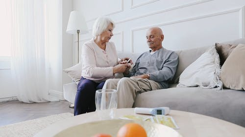 Medium Shot of an Elderly Woman Checking for Temperature of an Elderly Man