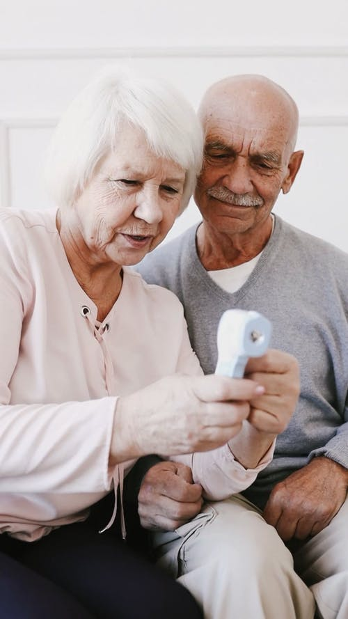Video of an Elderly Man and Elderly Woman Sitting While Using a Digital Thermometer