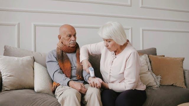 Elderly Couple Using Temperature Gun