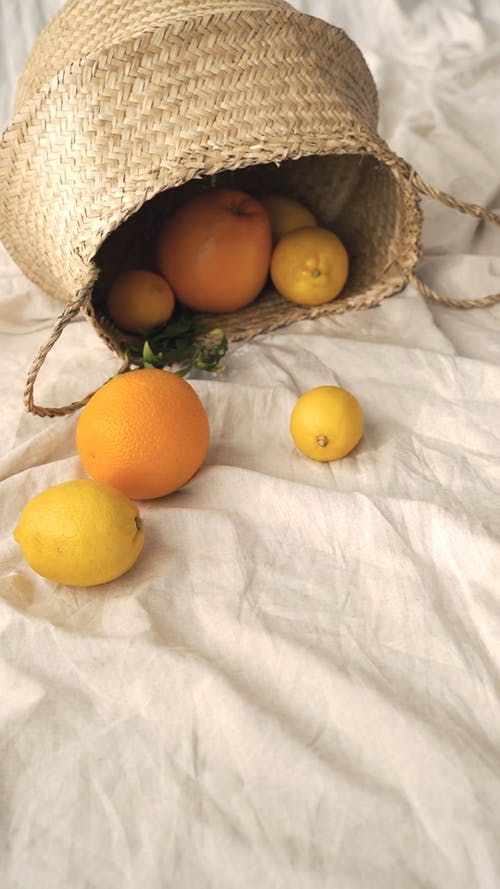 Basket of Citrus with a White Textile in the Background