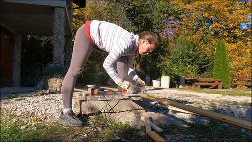 Woman Cutting and Fixing Wooden Planks at her Home