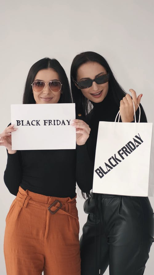 Woman in Black Long Sleeve Shirt Holding White Printer Paper While the Other is Holding a White Paper Bag with Black Friday Wording