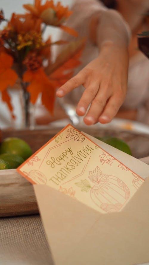 A Woman Reading a Thanksgiving Card