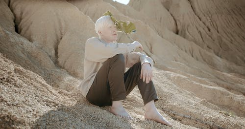 Man Sitting in the Desert Holding a Leaf