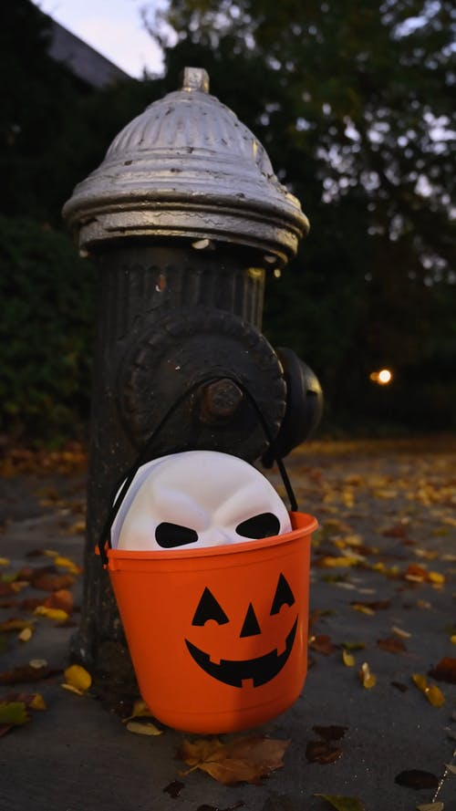 Halloween Mask in Bucket Hanging in a Fire Hydrant