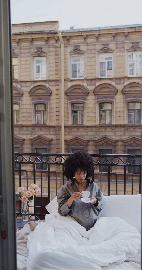 Pregnant Woman Drinking Coffee on the Balcony