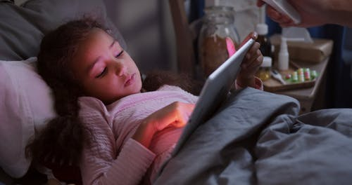 Little Girl Using Digital Tablet while Having Temperature Checked