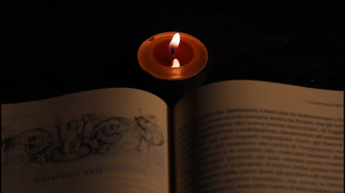 Burning Candle in Front of a Book