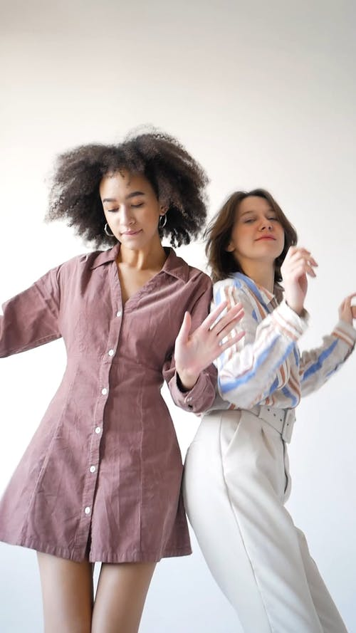 Young Women Dancing Back to Back and Looking at Camera