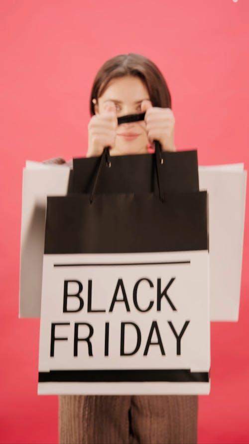 Женщина показывает свои сумки на шоппинге в Черную пятницу