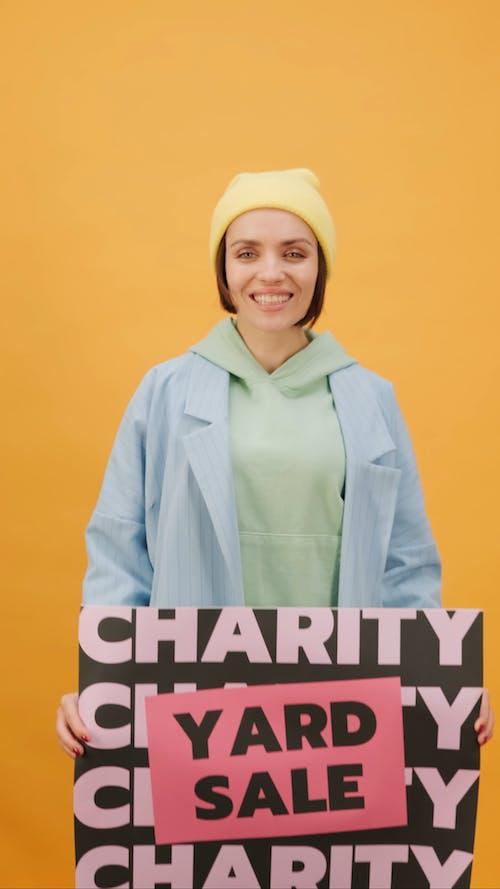 Bir Yardım Yard Satış Poster Tutan Bir Kadın