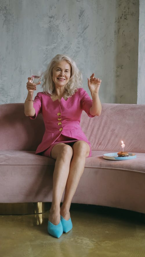 Elderly Woman Celebrating while Sitting in the Couch