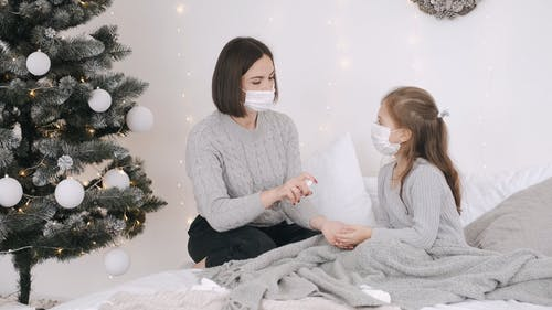 Woman Spraying Sanitizer In Girl's Hand