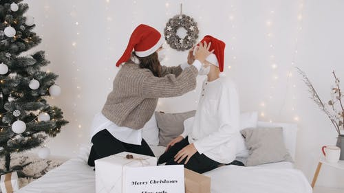 Woman Fixing Santa Claus Hat On Another Person
