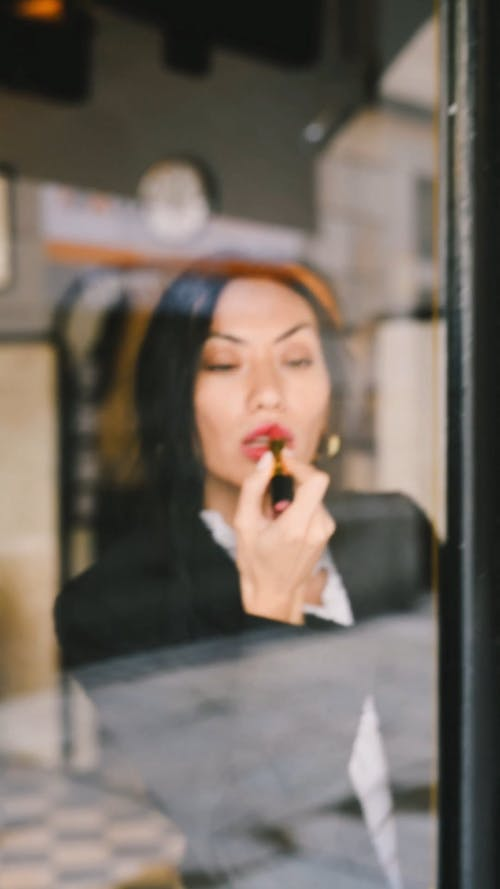 Woman Using Red Lipstick