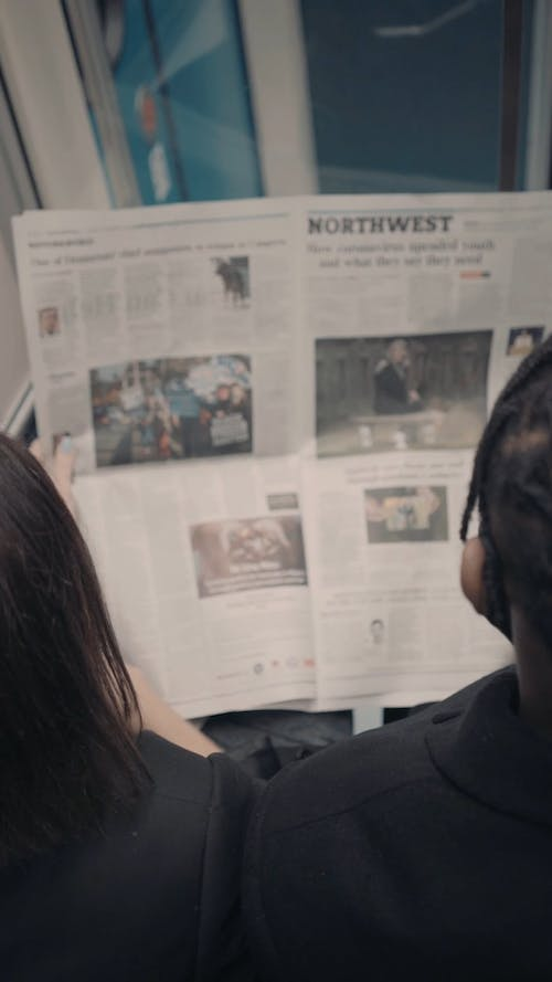 Young Woman and Man Reading Newspaper in Metro Top View