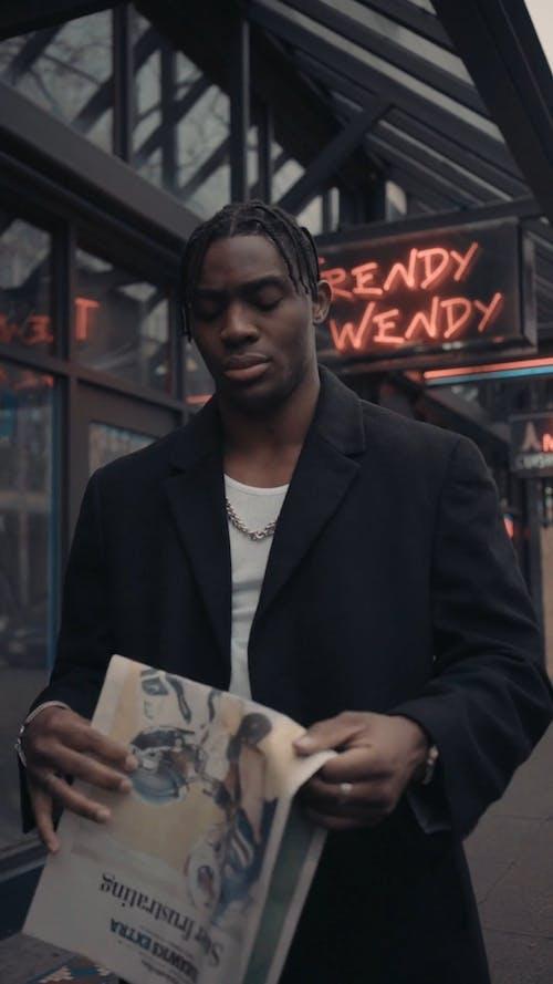Man Putting Newspaper Inside His Coat